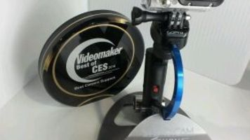 blue handheld stabilizer with action camera and award