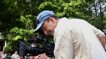 a cameraman bending over a camera focusing and framing a shot