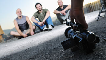 Camera on the ground pointing at three people sitting on the ground