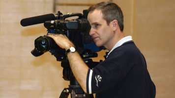 Man operating a large camcorder
