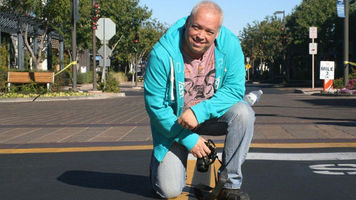 Man in a crosswalk with a camera