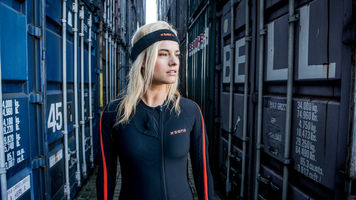 Woman wear a motion capture suit walking by metal storage crates