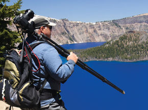 man-holding-camera-on-a-tripod-backpack-in-the-field