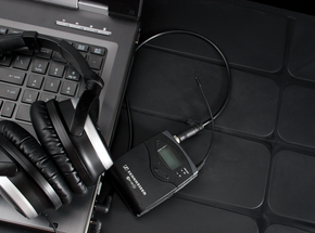 Closeup of headphones and a small lav mic on a laptop keyboard