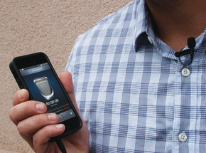 A man wearing a microphone and holding a mobile phone with an audio software program in the interface.