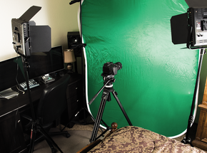 LED Lights, DSLR camera, green screen and editing computer in a small bedroom.