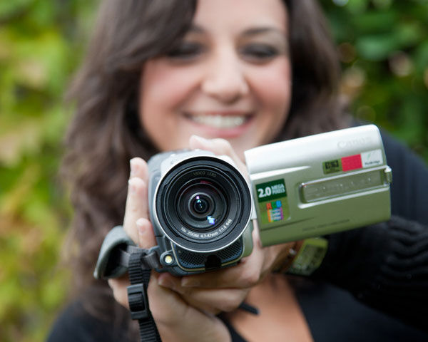 smiling-woman-holding-consumer-style-camcorder