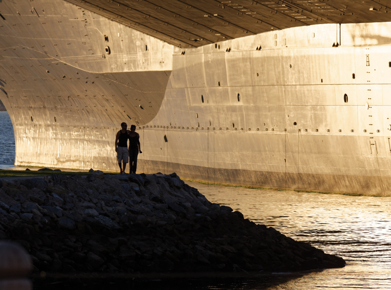 Shot of a well-lit large ship entering dock with two people who are backlit watching.