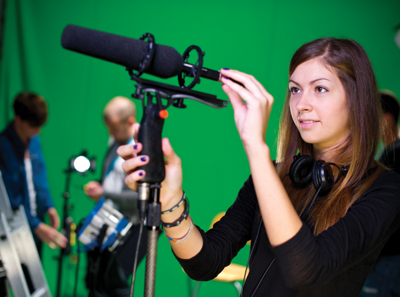 Shot of a young woman putting a shotgun mic into a boom holder.