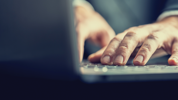 Photo of hands resting on a computer keyboard.