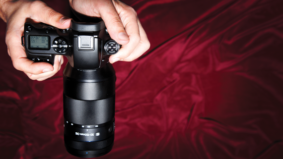 Interchangeable Lens Camera held over red background