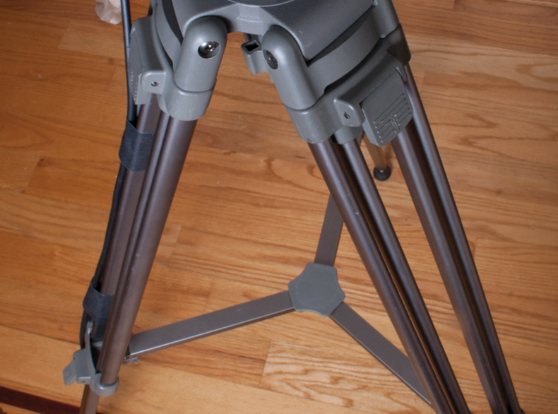 gray tripod legs with spreader and cable taped to it