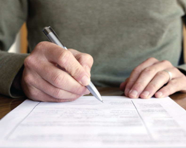 man-writing-on-paper-at-desk