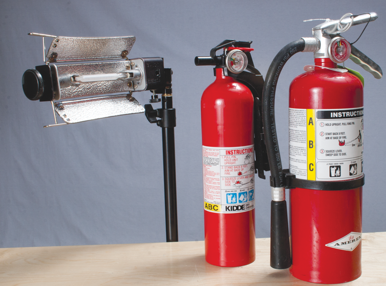 Shot of a large tungsten light with two fire extinguishers on a nearby table.