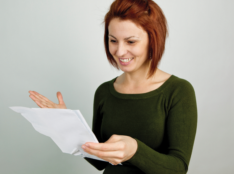 A woman smiling as she reads copy