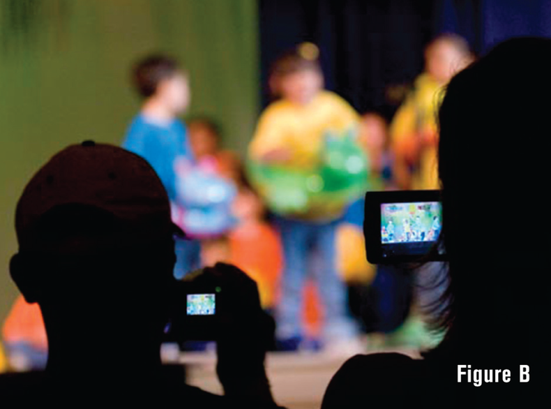 Shooting a school event, the stage is in soft focus while the parents are in focus but silhouetted.
