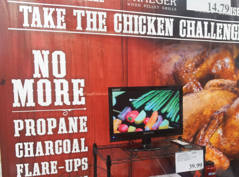 Shot of a display of barbeques with food-enticing video on a screen.