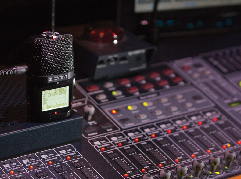 A Zoom audio recorder on a mixer board