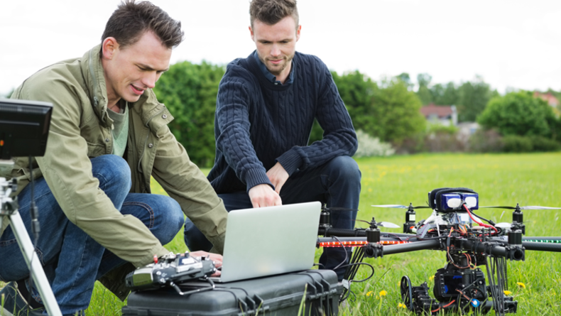 Technicians Using Laptop By Tripod And Drone