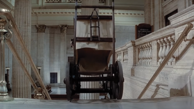 The baby carriage's starts it's journey down the stairs.