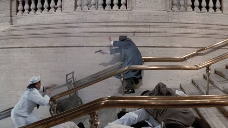Ness follows the baby carriage down the stairs while shooting at thugs.