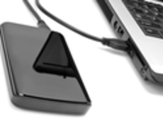 Shot of an external hard drive hooked up to a laptop.