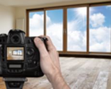 Man shooting empty living room with digital camera