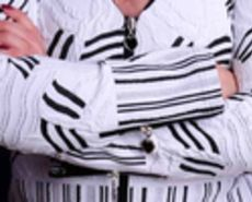 A woman with crossed arms wearing a busy striped shirt