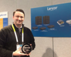 A man holds an award next to a product banner