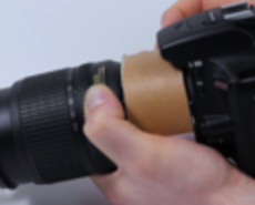 Camera and lens separated by cardboard tube pointed at broccoli