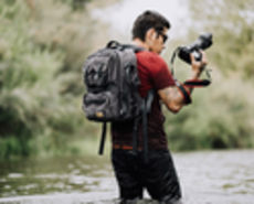 Man in water with camera bag