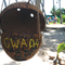 """A coconut shell with the yellow painted word, """"Gwada"""", hanging from a bit of twine on the open door of a palm frond tree hut."""
