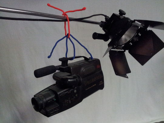Gear ties holding an old camera attached to a C-stand