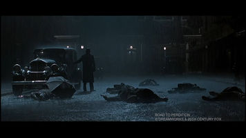 Still frame from the movie Road to Perdition, dead bodies on the ground, Paul Newman's character standing alone