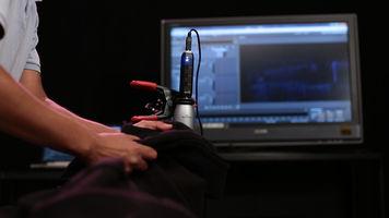 Foley artist using sweatshirt near mic to create sound