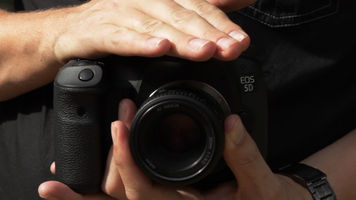 Shot of a Canon 5D Mark II with a Nikon 50mm F mount lens being handheld to the body